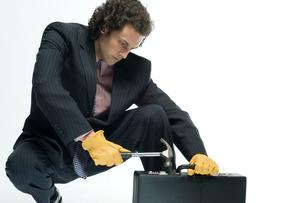 アタッシェケースをこじ開けようとするビジネスマンの写真素材 [FYI04070946]