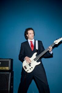 スーツ姿でギターを弾くビジネスマンの写真素材 [FYI04070947]