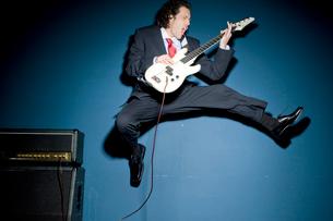 ギターを弾きながらジャンプするビジネスマンの写真素材 [FYI04070950]