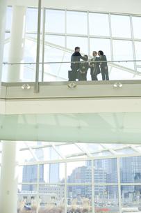 オフィスビルで立ち話をするスーツ姿の男女の写真素材 [FYI04070955]