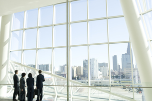 オフィスビルで立ち話をするスーツ姿の男女の写真素材 [FYI04070956]