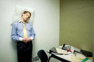 オフィスで仮眠をとるビジネスマンの写真素材 [FYI04070964]