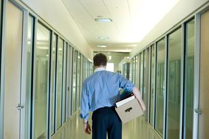 ダンボール箱を手にしてオフィスを去るビジネスマンの写真素材 [FYI04070965]
