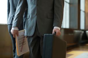 機密書類を手渡しするスーツ姿の男女の写真素材 [FYI04070975]