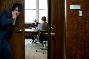 オフィスの前で盗聴するビジネスウーマンの写真素材 [FYI04070976]