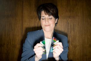 CDを両手で割るビジネスウーマンの写真素材 [FYI04070977]