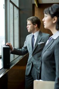 オフィスで外を眺めるスーツ姿の男女の写真素材 [FYI04070980]