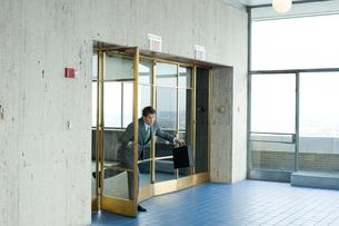 オフィスの入口から飛び出すビジネスマンの写真素材 [FYI04070981]