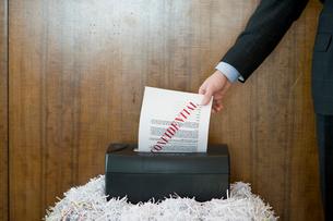 機密書類をシュレッダーにかけるビジネスマンの写真素材 [FYI04070984]
