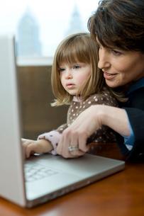 オフィスでパソコンを見つめる母親と娘の写真素材 [FYI04070985]