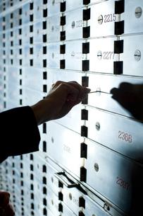 郵便受けの鍵を開けるビジネスマンの写真素材 [FYI04070990]