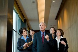 オフィスを歩くビジネスマンと傍を歩く男女の写真素材 [FYI04070993]