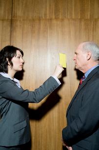 イエローカードを男性につきつけるビジネスウーマンの写真素材 [FYI04070997]
