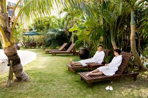テラスの寝椅子でくつろぐ男性と女性の写真素材 [FYI04071015]