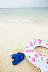 砂浜に置かれた浮き輪とビーチサンダルの写真素材 [FYI04071030]