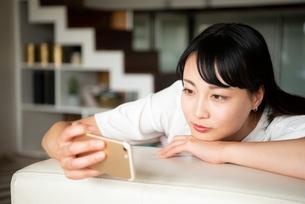 スマホで動画を見ている女性の写真素材 [FYI04073022]