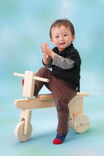 木の三輪車に乗って笑う男の子の写真素材 [FYI04073628]