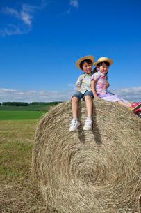 大きな干し草ロールの上の兄妹の写真素材 [FYI04073657]