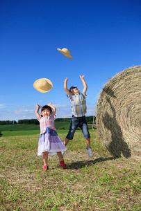 大きな干し草の横でジャンプする兄妹の写真素材 [FYI04073662]