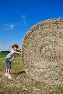 大きな干し草ロールを押す男の子の写真素材 [FYI04073663]