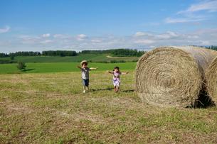大きな干し草ロールの横を走る兄妹の写真素材 [FYI04073666]