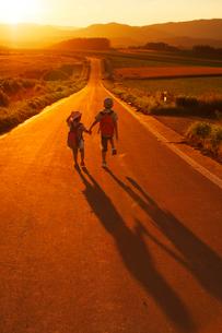 夕暮れの道を歩いて帰る兄妹の写真素材 [FYI04073672]