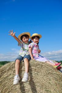 大きな干し草ロールの上の兄妹の写真素材 [FYI04073678]