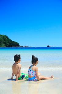波打ち際に座る水着を着た兄妹の写真素材 [FYI04073688]