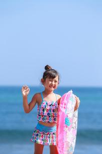 海で浮き輪を持って手をふる女の子の写真素材 [FYI04073694]