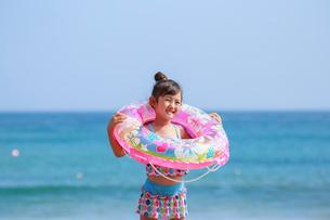 海で浮き輪を持って笑う女の子の写真素材 [FYI04073695]