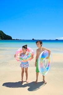 海で浮き輪を持って笑う兄妹の写真素材 [FYI04073697]