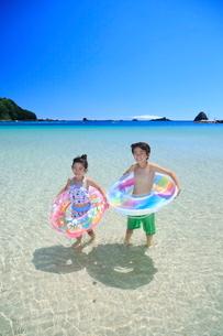 海で浮き輪を持って笑う兄妹の写真素材 [FYI04073698]