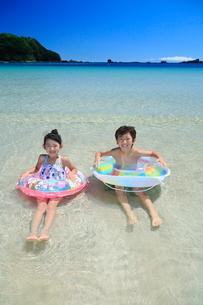 波打ち際で浮き輪を持って遊ぶ兄妹の写真素材 [FYI04073700]