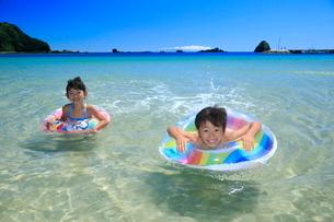 海で浮き輪を使って泳ぐ兄妹の写真素材 [FYI04073702]