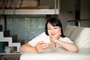 スマホで動画を見ている女性の写真素材 [FYI04073902]