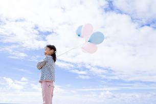 青空と風船を持っている女の子の写真素材 [FYI04075247]