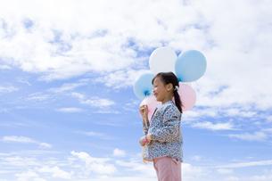 青空と風船を持っている女の子の写真素材 [FYI04075248]