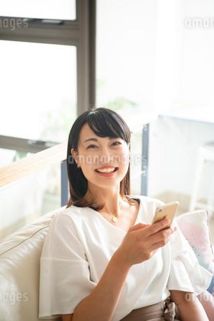 スマホを手に持って笑っている女性の写真素材 [FYI04075608]