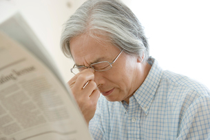 新聞を読み目頭を押さえるシニア男性の写真素材 [FYI04076304]
