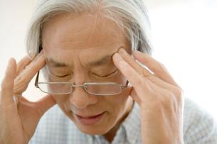 頭痛をこらえるシニア男性の写真素材 [FYI04076306]