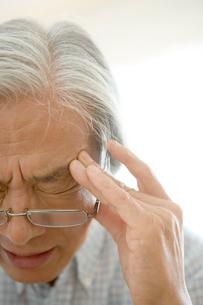 頭痛をこらえるシニア男性の写真素材 [FYI04076307]