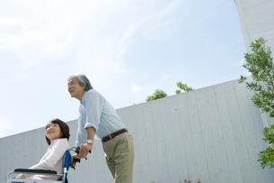 庭で車いすに座る妻を支える夫の写真素材 [FYI04076309]