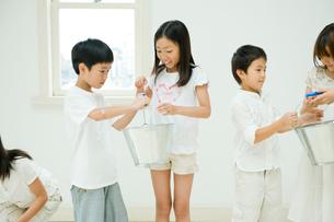 バケツリレーをする2人の男の子と3人の女の子の写真素材 [FYI04076412]