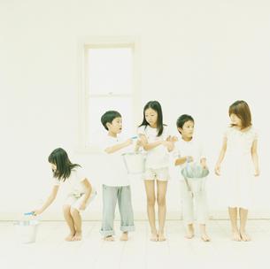 バケツリレーをする2人の男の子と3人の女の子の写真素材 [FYI04076413]