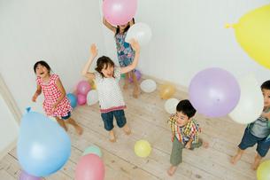 風船で遊ぶ2人の男の子と3人の女の子の写真素材 [FYI04076436]