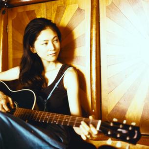 ギターを弾く日本人女性の写真素材 [FYI04076491]