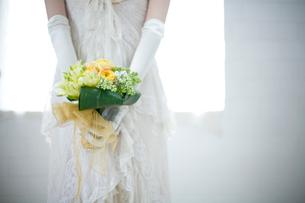 後ろ手にブーケを持つ花嫁の後姿の写真素材 [FYI04076633]