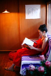 ソファーで画集を見る女性の写真素材 [FYI04076662]