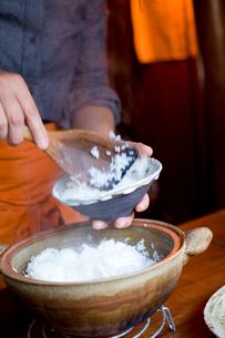 土鍋からごはんをよそう女性の手元の写真素材 [FYI04076679]