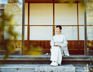 縁側でお茶をする和服の女性の写真素材 [FYI04076686]